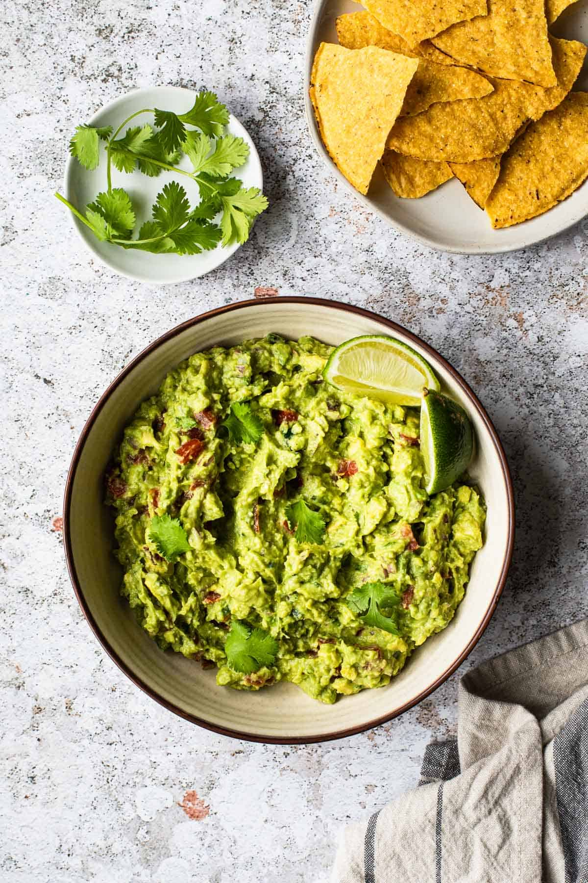 overhead view of a bowl of guacamole with cilantro leaves and chips in the background