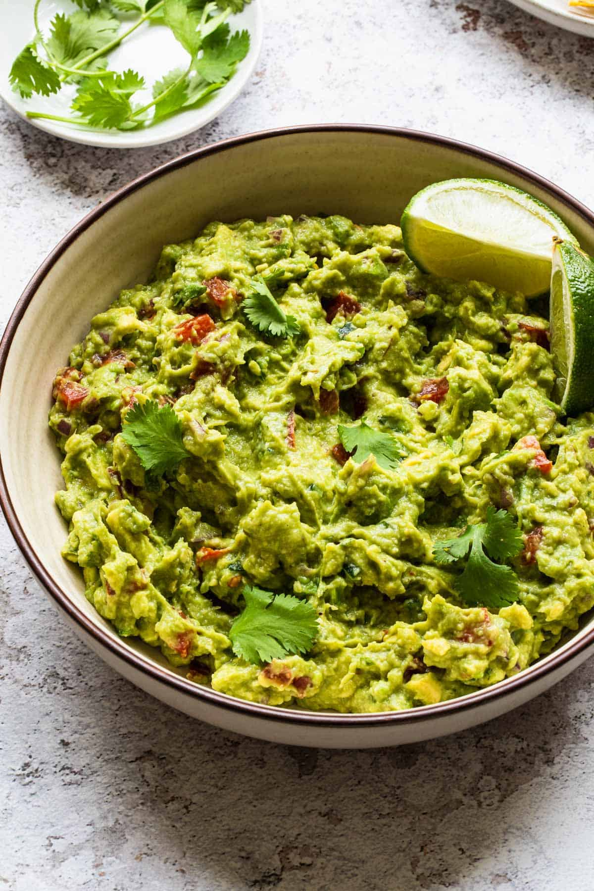 close up view of bowl of guacamole with cilantro leaves in background