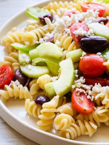 back lighting on a white plate of pasta salad
