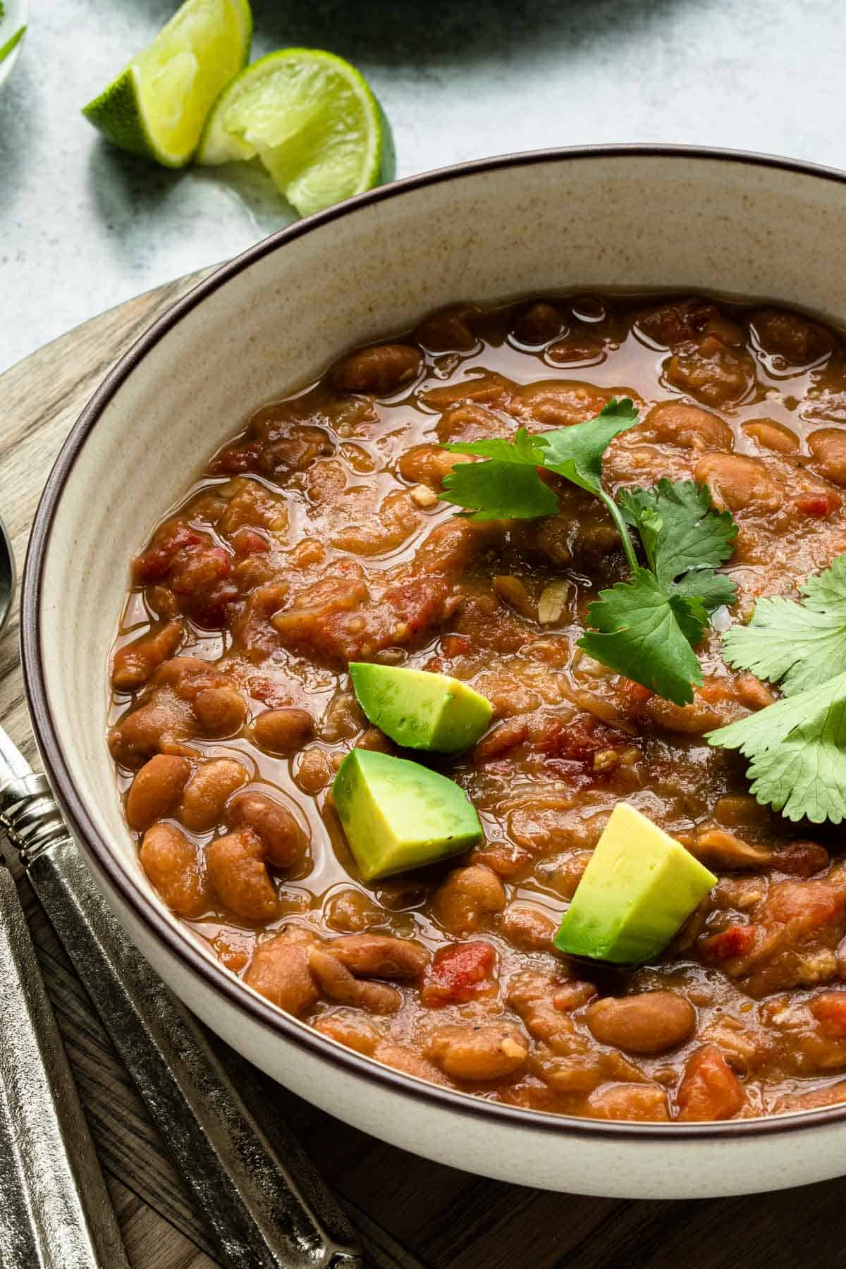close up view of cooked pintos in a bowl with cilantro leaves and diced avocado
