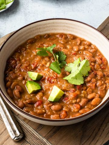 bowl of pinto beans on a wooden board with spoons to the left