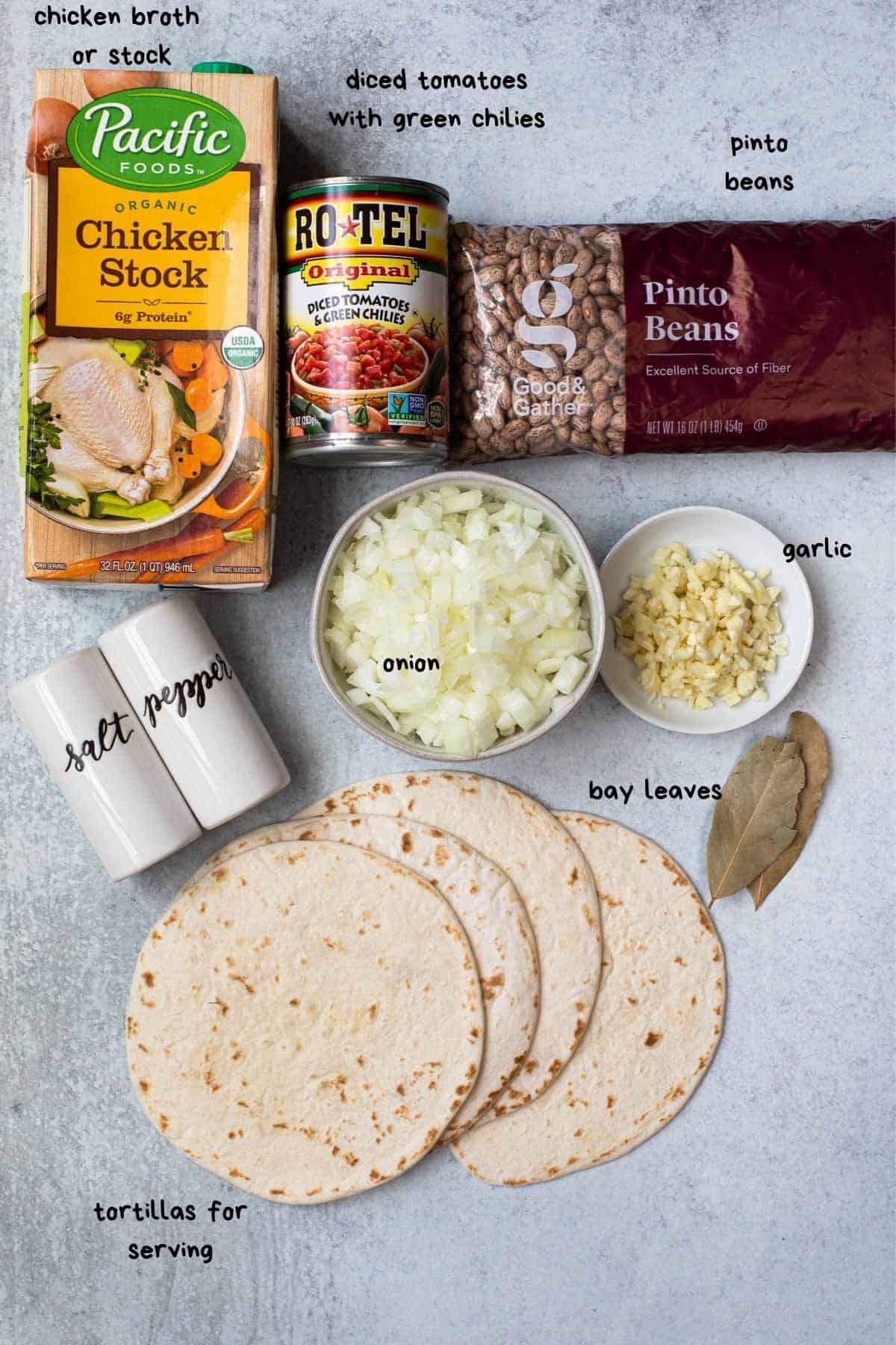 flat lay view of ingredients like chicken broth, chopped onions and garlic
