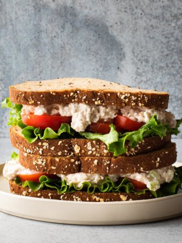 close up of 2 chicken salad sandwiches stacked on a plate
