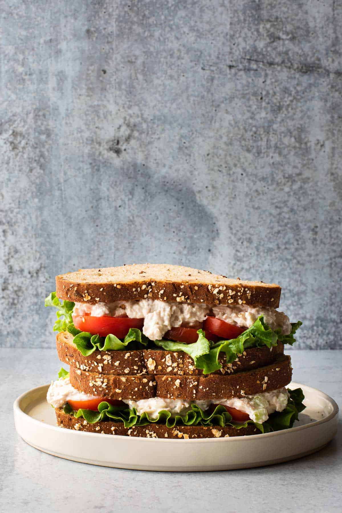 two sandwiches stacked on top of each other on a white plate with a gray background