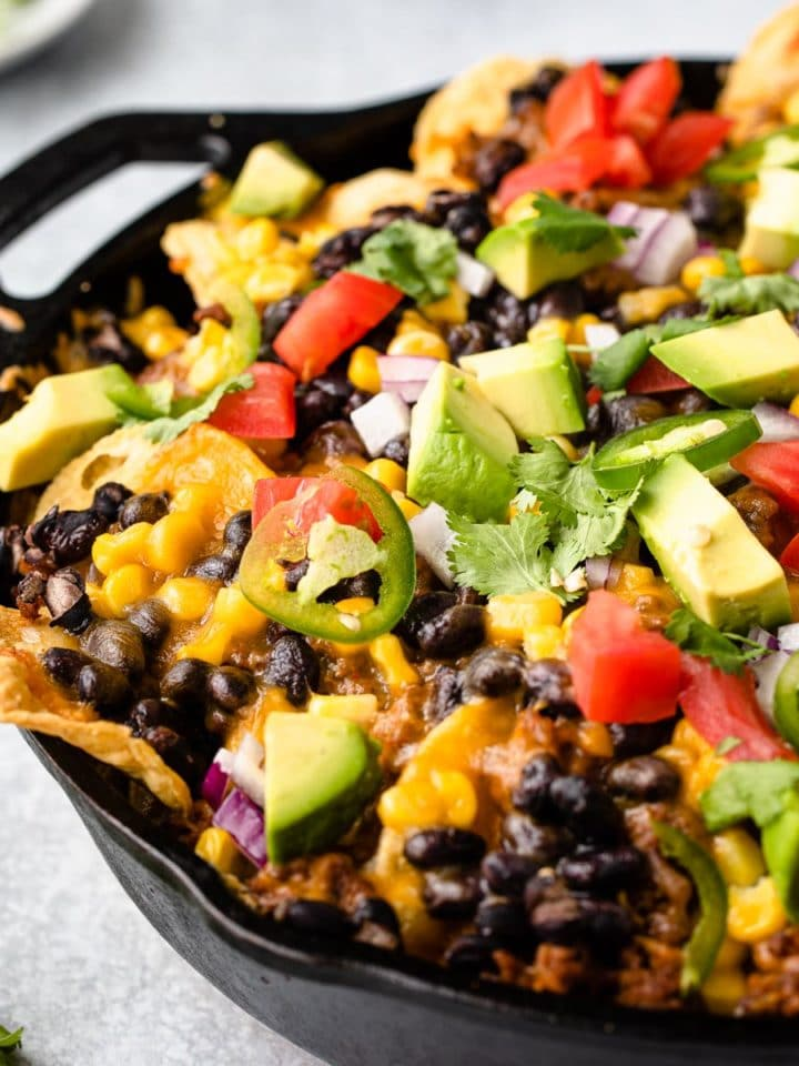 close up view of nachos in a cast iron skillet loaded with garnishes