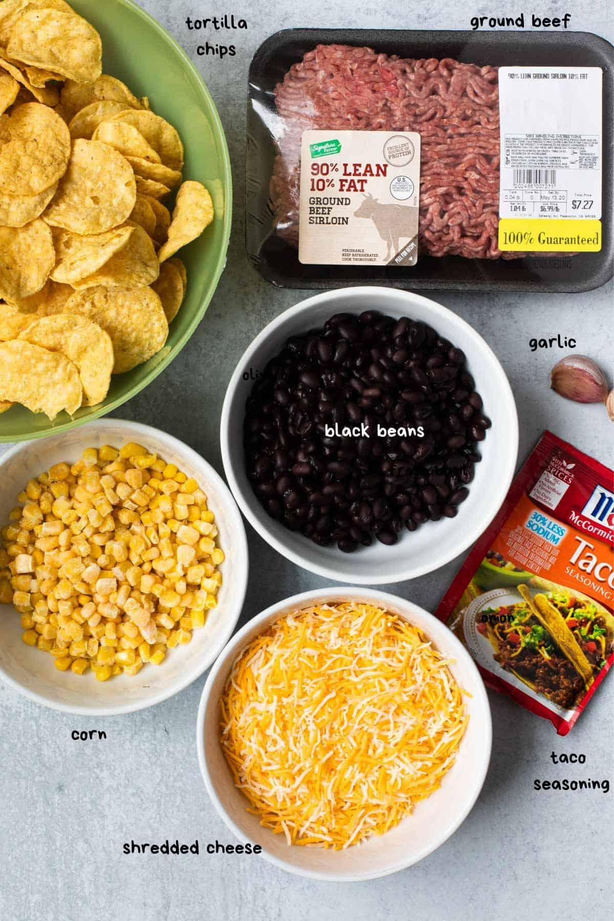 overhead photo showing chips, corn, shredded cheese, black beans, taco seasoning, and uncooked ground beef