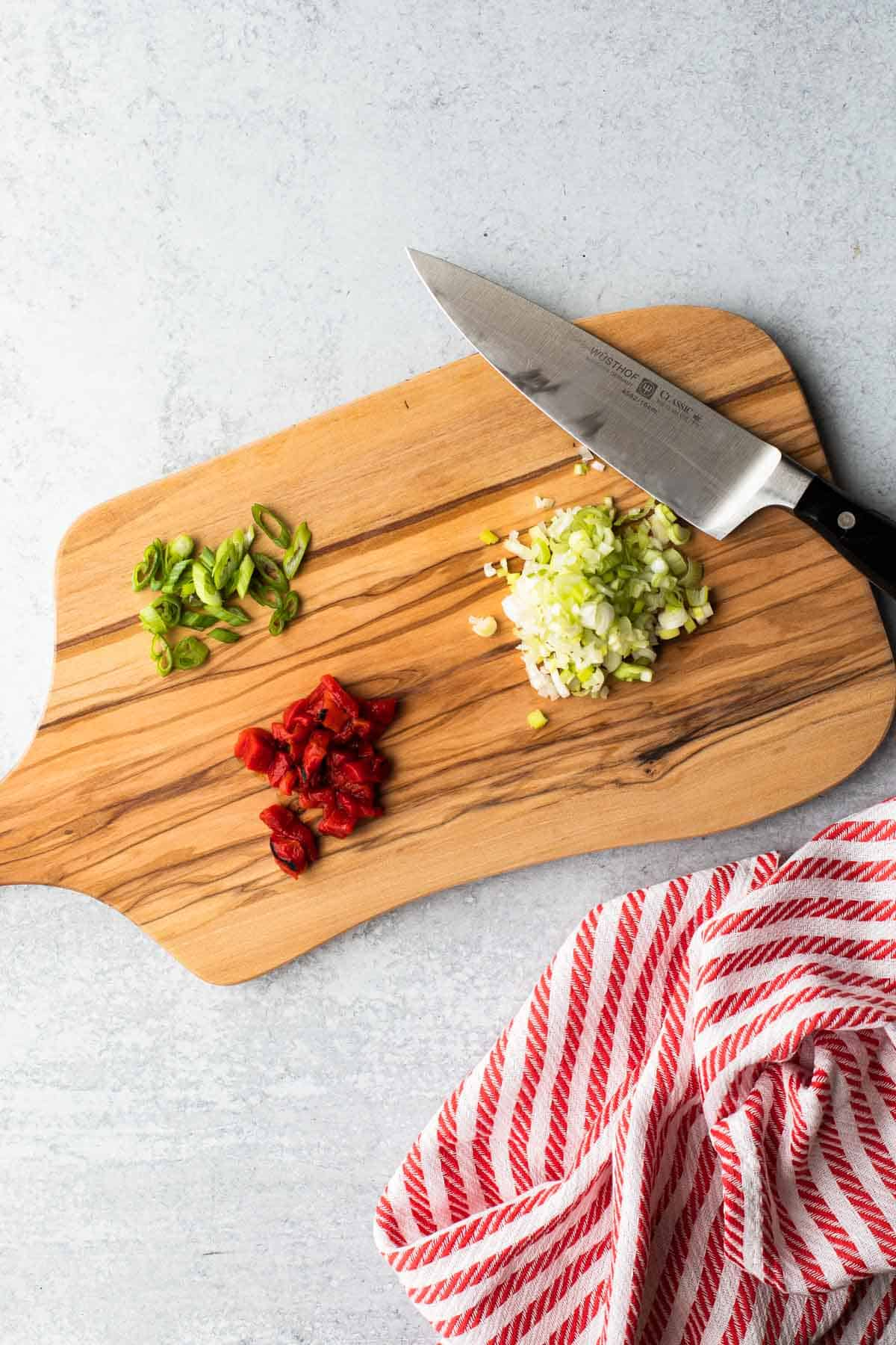 cutting board with chopped peppers and green onion-knife and towel