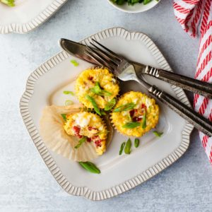 overhead shot of 3 breakfast egg cups on a plate with a fork and knife