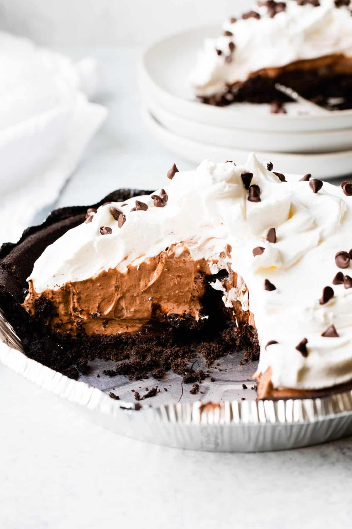 a chocolate pie topped with whipped cream with a slice taken out and set in background