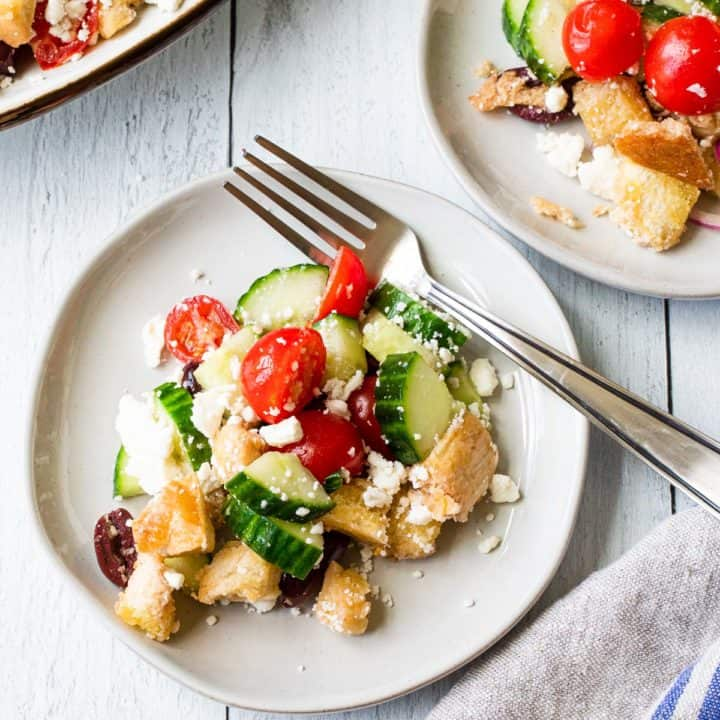 panzanella on a white plate with a fork and a small plate in background