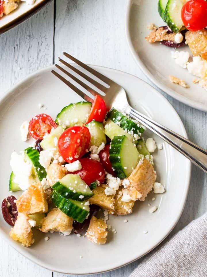 mediterranean bread salad on a white plate with a fork and a small plate in background