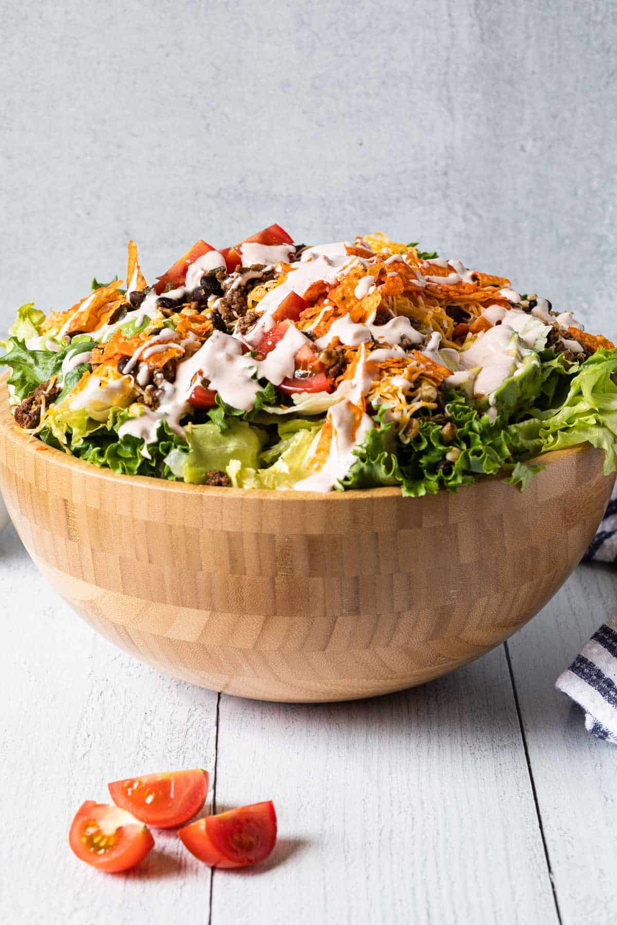 a large wooden bowl overflowing with taco salad drizzled with creamy dressing