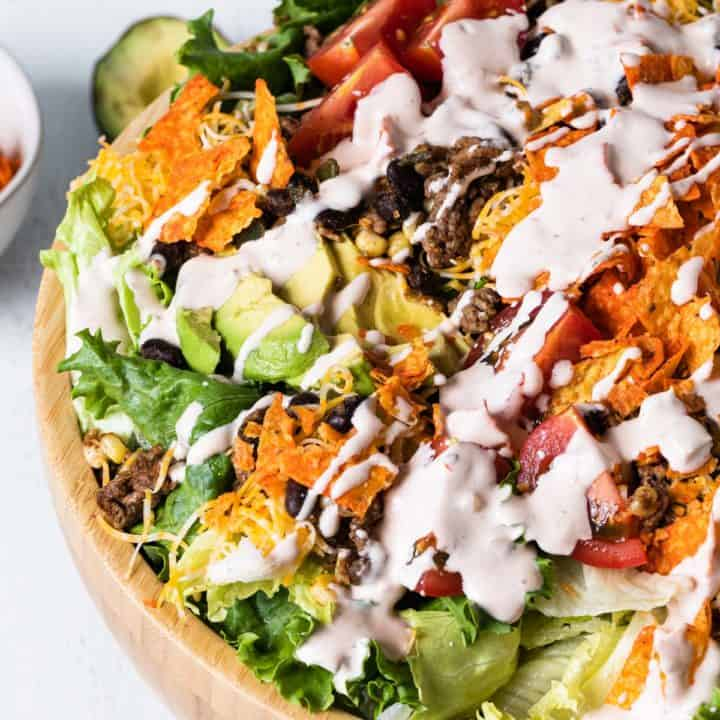 close up overhead view of wooden bowl filled with salad drizzled with creamy dressing
