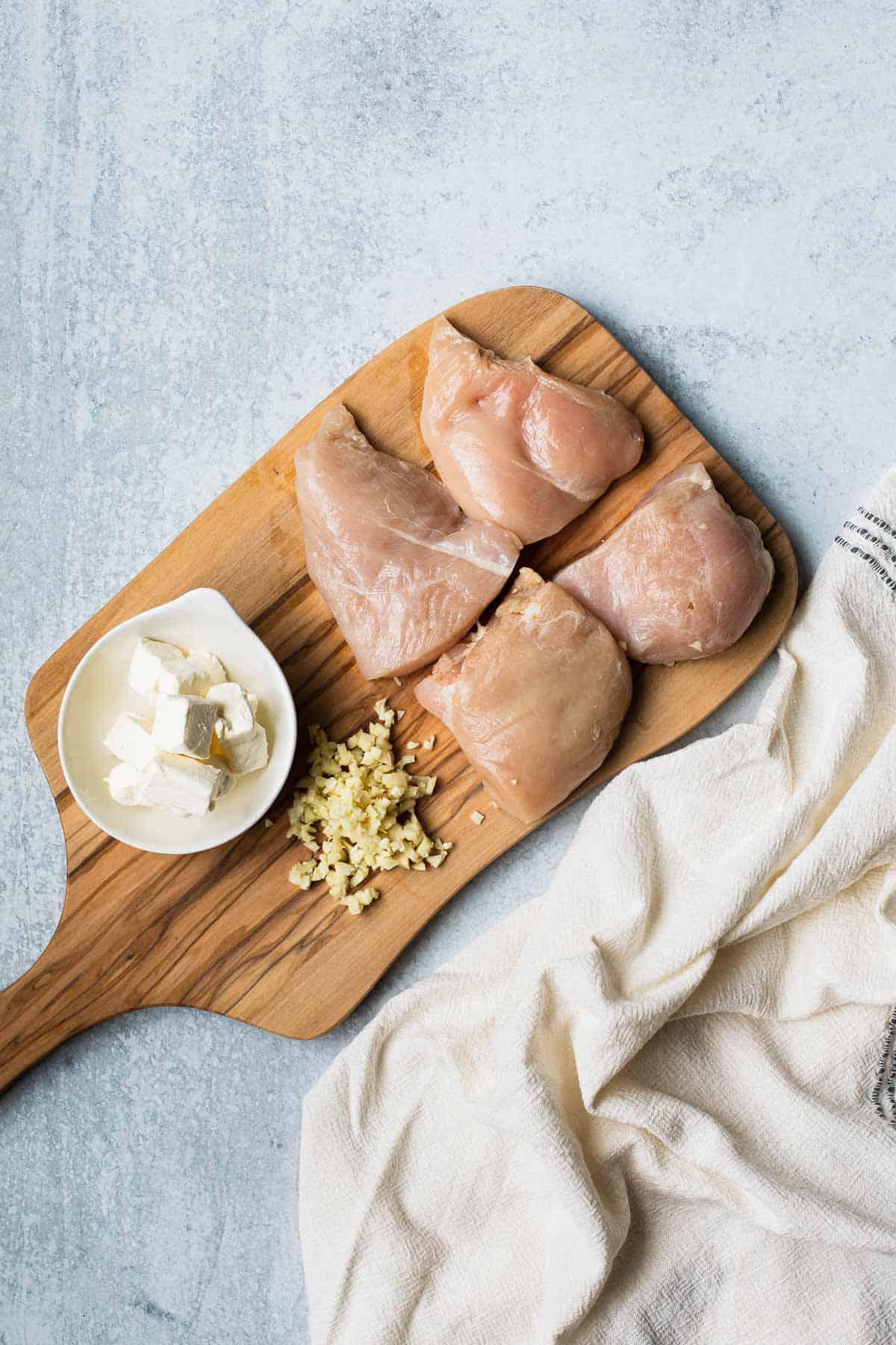 cut chicken, minced garlic, cubed cream cheese on a cutting board
