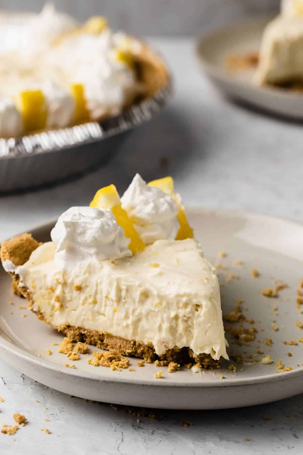close up view of a slice of lemon pie on a white plate with whole pie in background