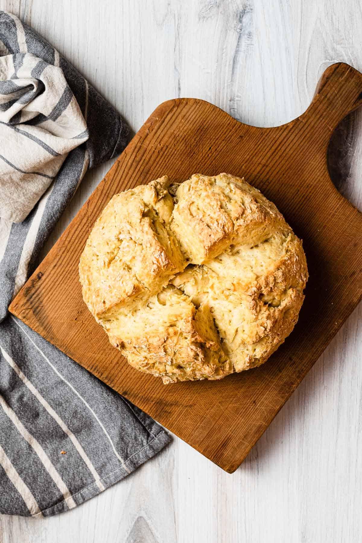 loaf of irish soda bread on a wooden cutting board