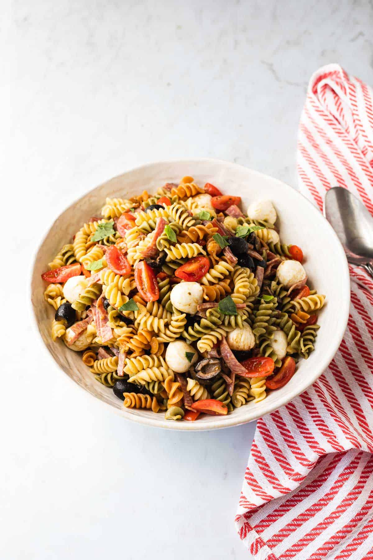 white bowl with a pasta salad in it, red and white striped towel on right side