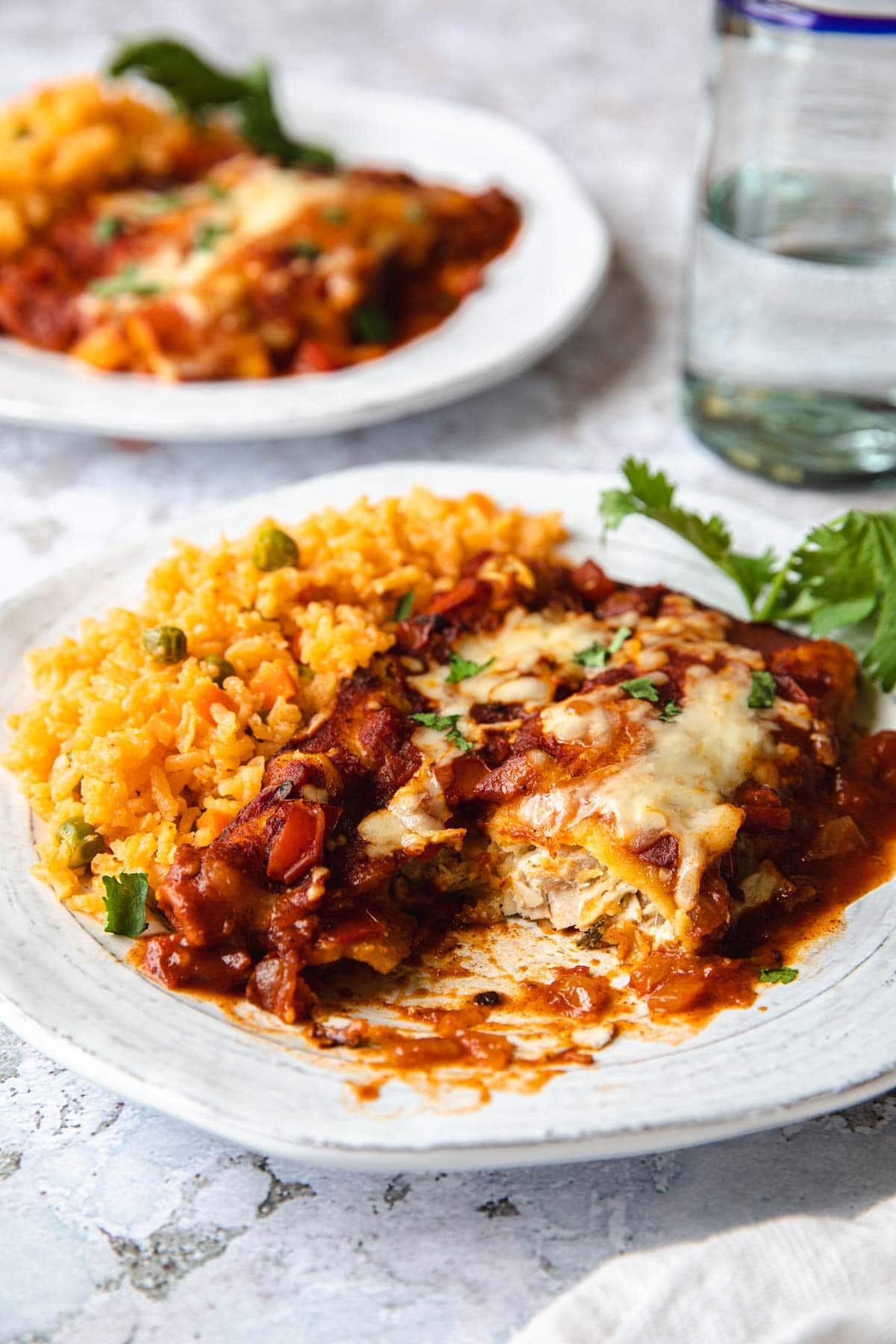 plate of enchiladas cut open to show chicken filling and a side of d spanish rice