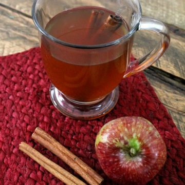 hot drink in a glass with cinnamon sticks on the side