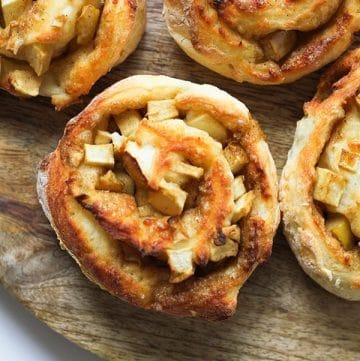 apple cinnamon roll on a wooden serving board.