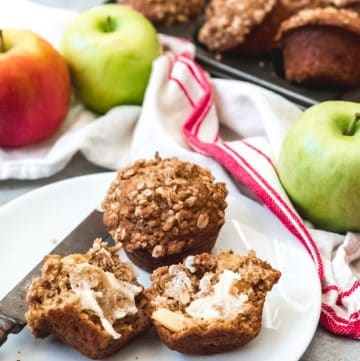 muffins on a white plate with apples in the background