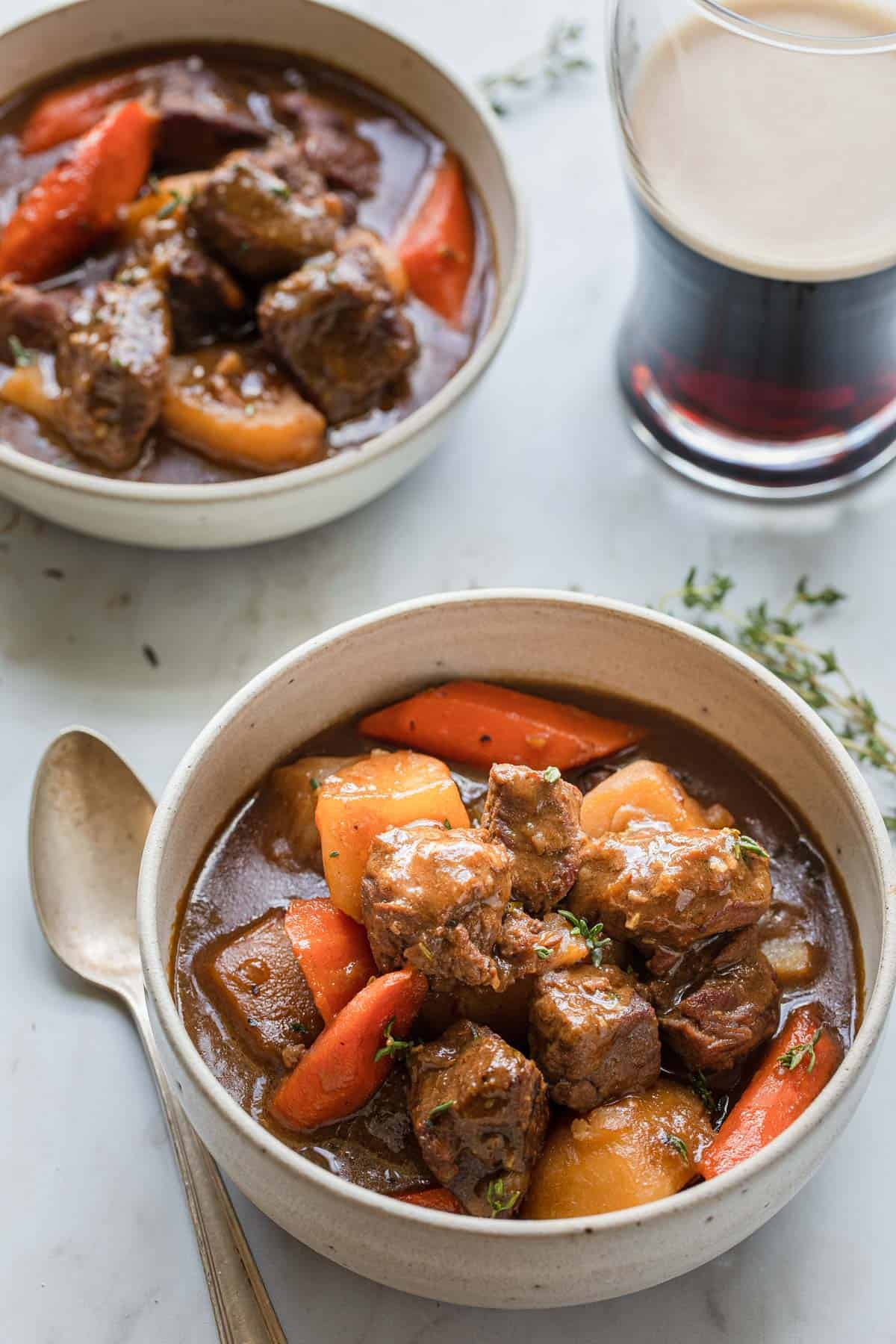 bowl of beef stew with a glass of dark beer in the background