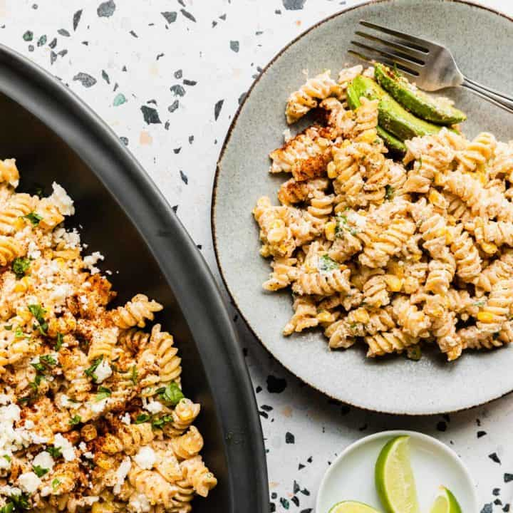 top down view of a plate of mexican street corn pasta salad with a partial view of large platter on right