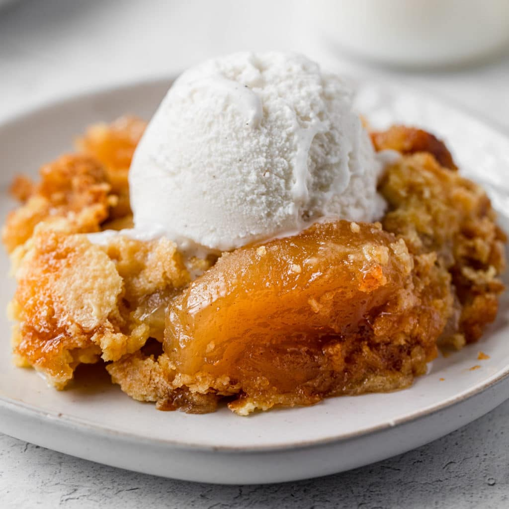 apple dump cake with a scoop of vanilla ice cream