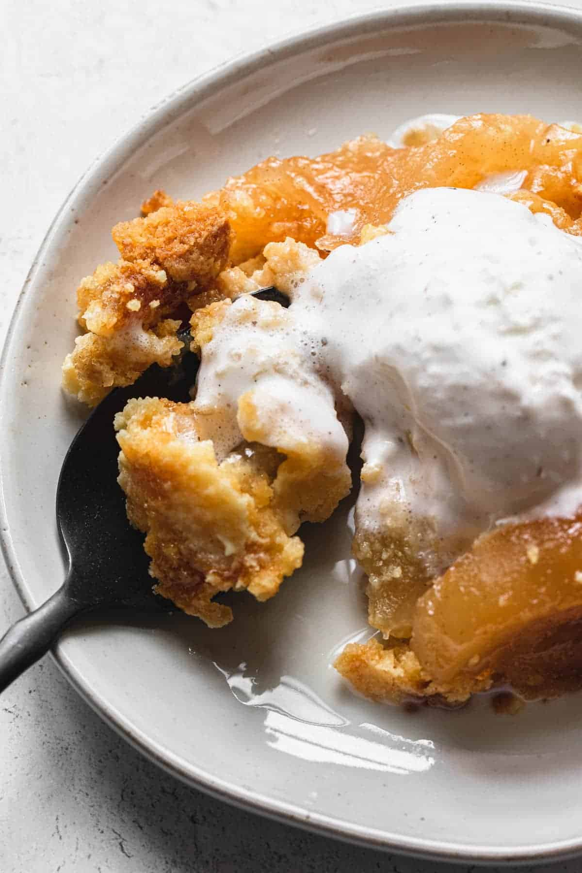 apple dump cake on a plate with melting vanilla ice cream and a spoon