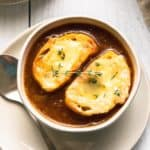 caramelized onion soup in a bowl with thyme and cheesy toasted bread
