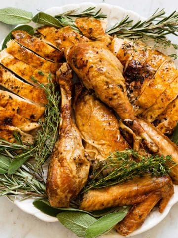 roasted turkey cut up on a platter with fresh herbs