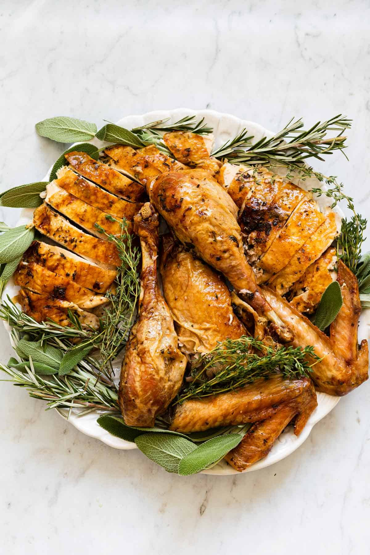 round platter with cut up roasted turkey and fresh herbs