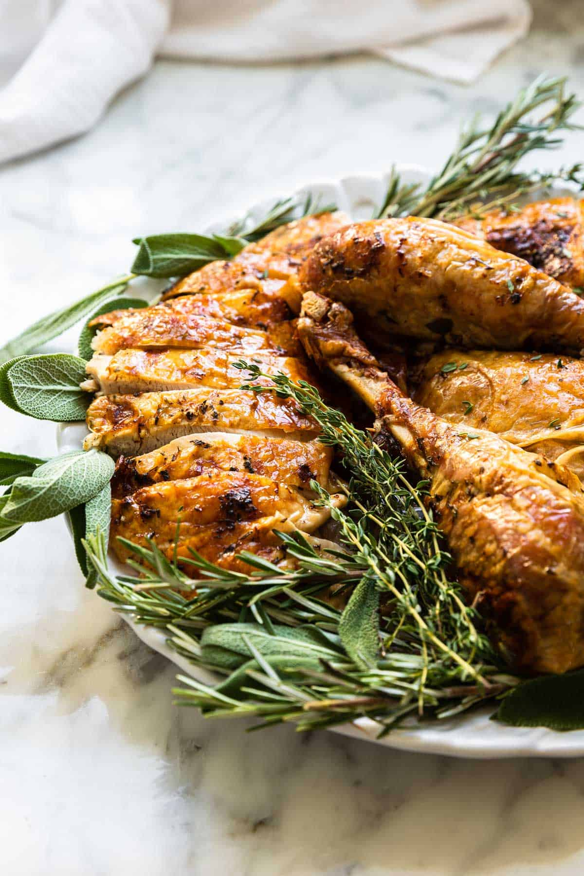 cut up pieces of sliced turkey surrounded by fresh herbs