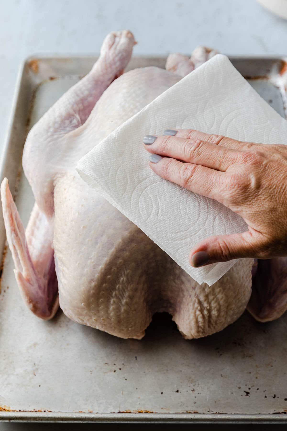 raw turkey being wiped with a paper towel