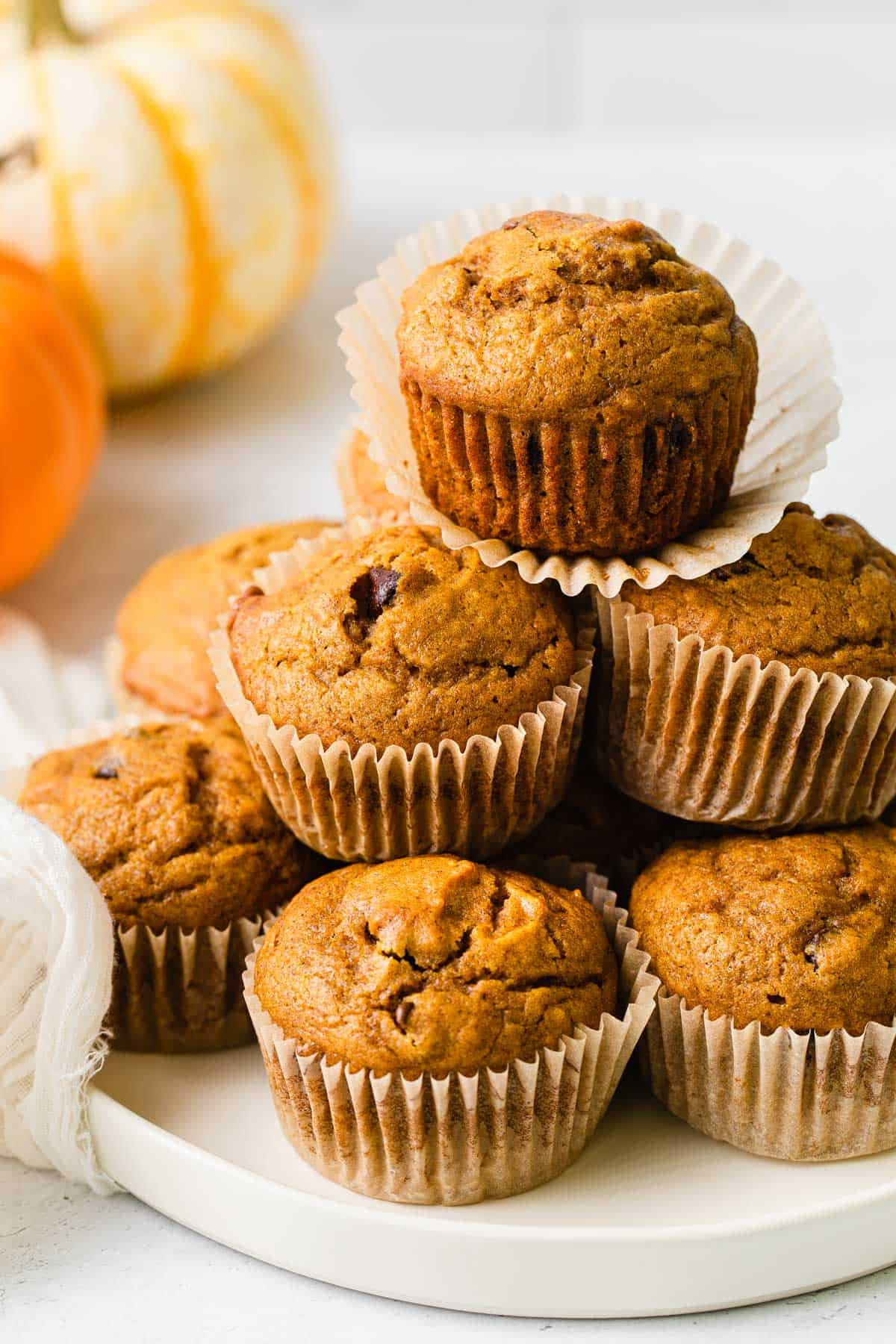 Pumpkin chocolate chip muffins stacked on a plate.