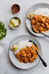chicken curry plated with rice and garnishes
