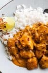 Chicken smothered in coconut curry sauce with a side of white rice and lime.