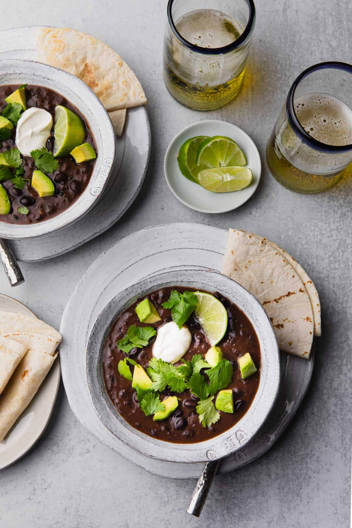 Two bowls of black bean soup topped with avocado and cilantro.