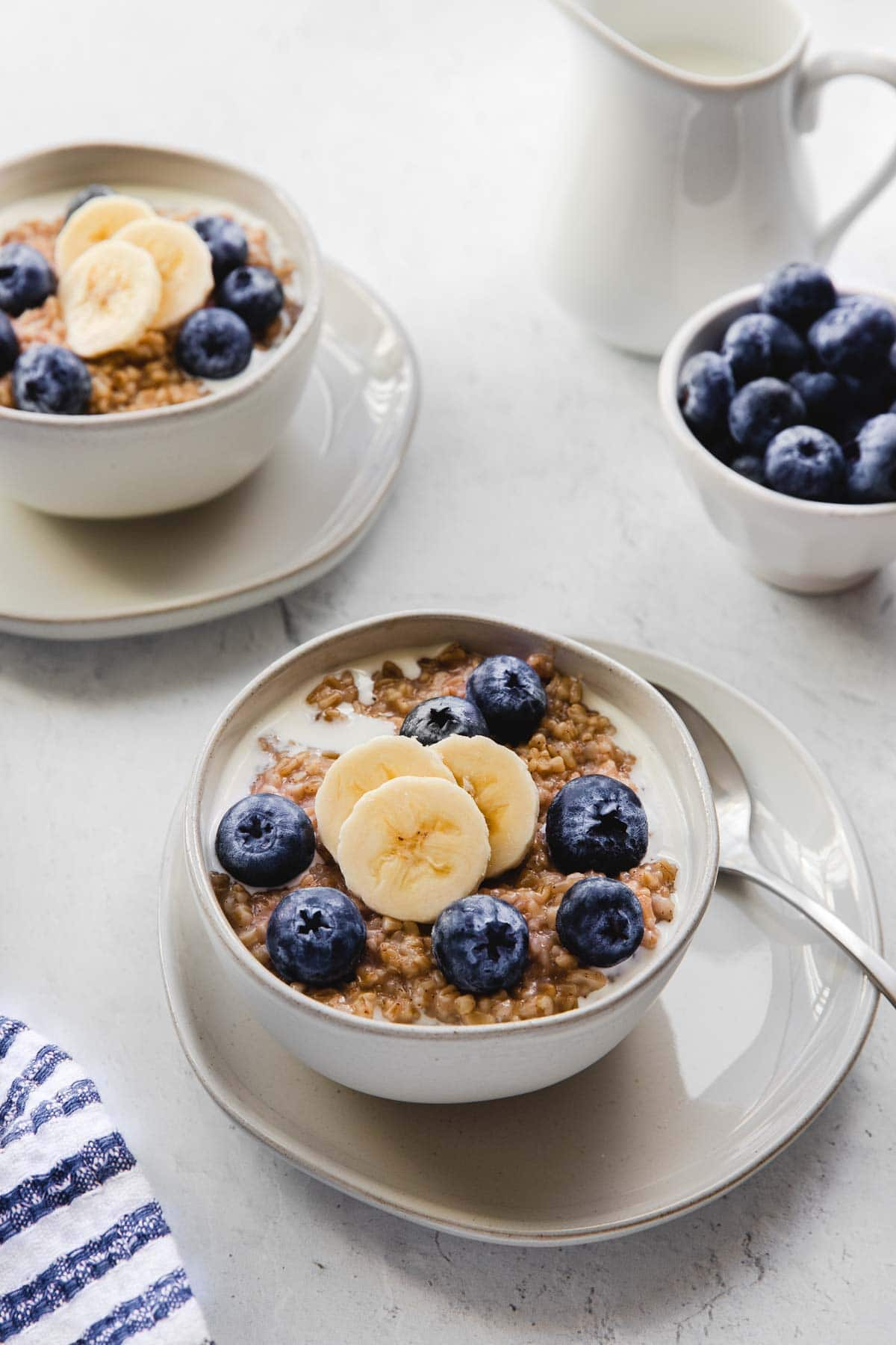 Steel cut oatmeal in a bowl with bananas and blueberries.