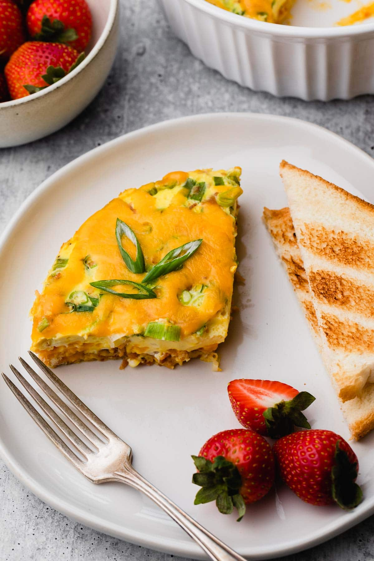 A plate of egg casserole, toast, and strawberries.
