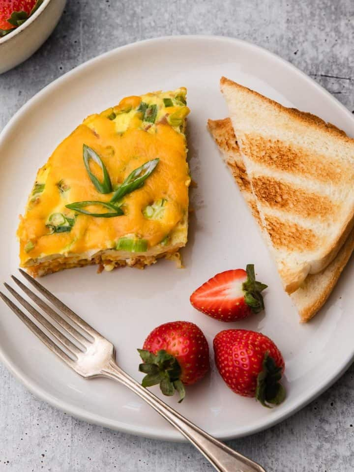 A plate of breakfast casserole, toast, and strawberries.
