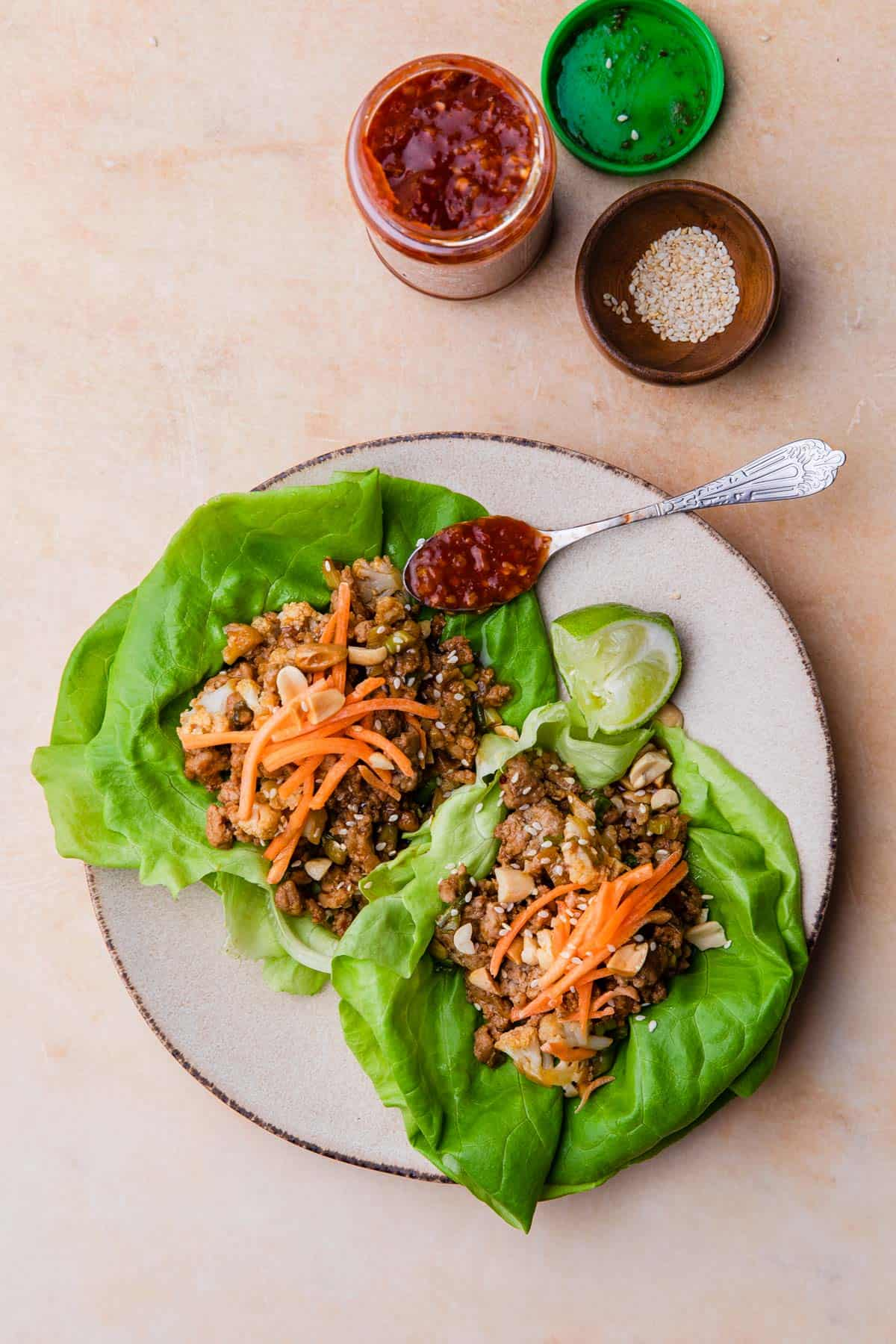 lettuce wraps on a plate with chili garlic sauce on the side