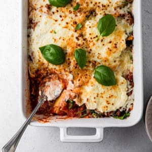 casserole dish with baked ravioli and basil leaves