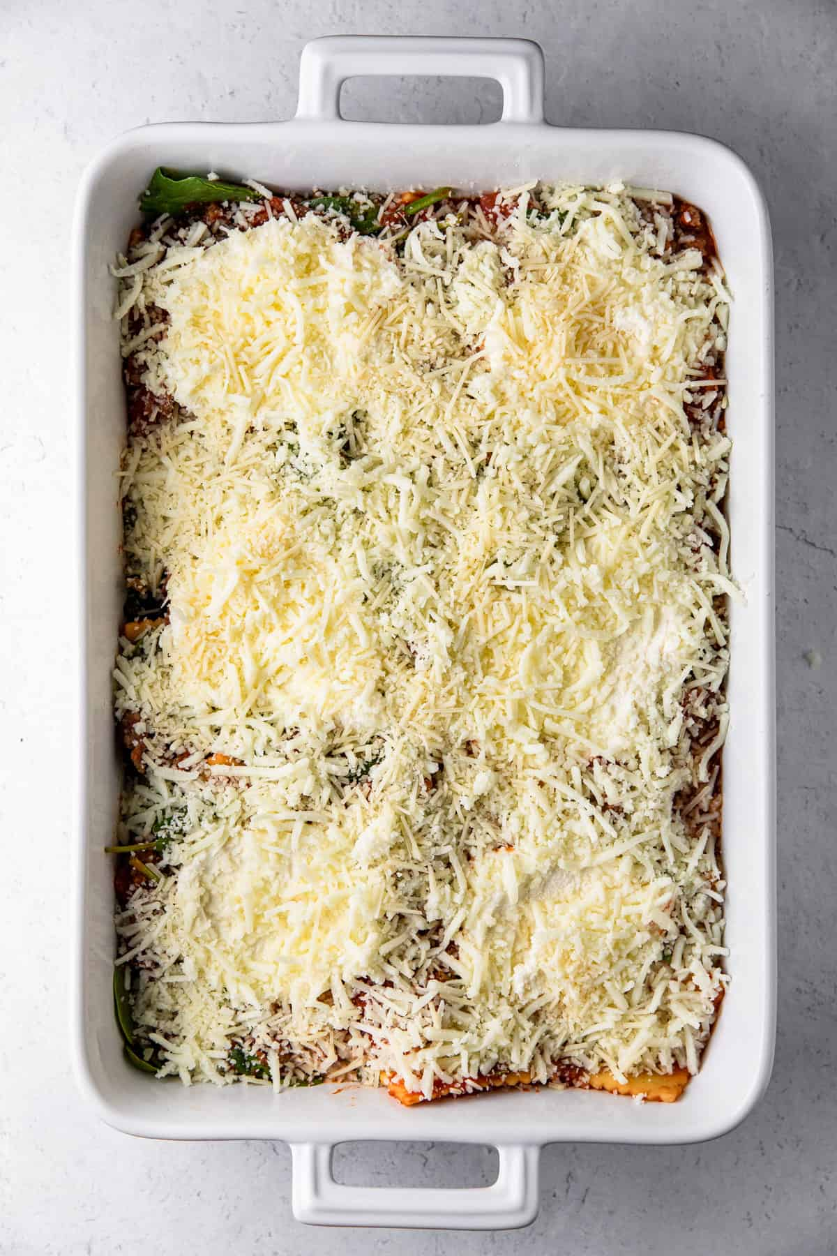 casserole dish with ravioli mixture, ricotta and shredded cheeses