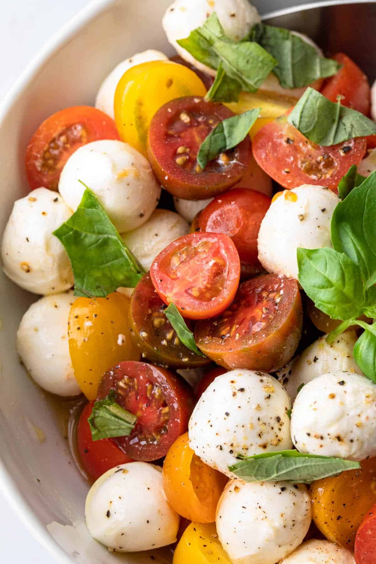 cherry tomatoes and mozzarella balls with basil leaves in a salad bowl