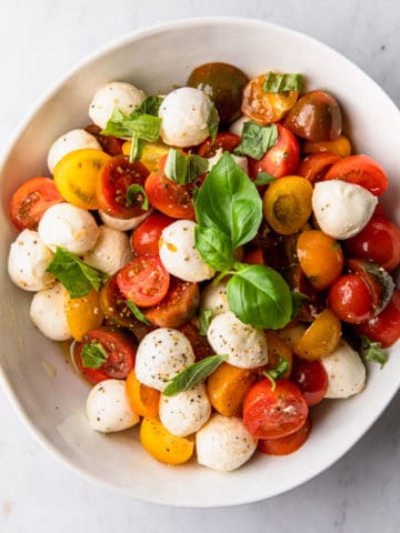 a large white bowl with a cherry tomato, mozzarella and basil salad