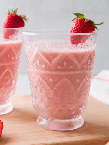 2 glasses filled with a pink strawberry oatmeal smoothie