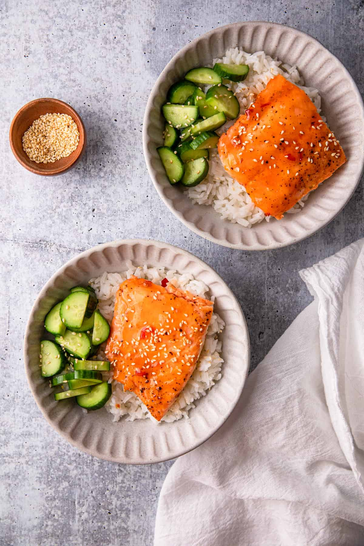 two bowls of sweet chili salmon over rice with cucumbers.