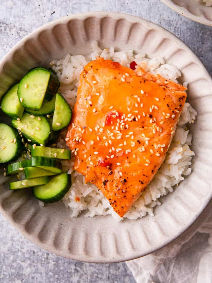 sweet chili salmon recipe prepared in a bowl over rice and cucumbers