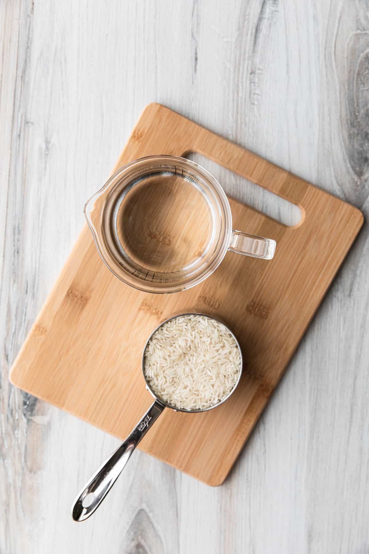 a cup of dry rice and a cup of water on a cutting board